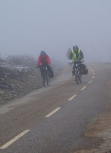 Cycling-pilgrims with snow and fog. descending to Manjarin